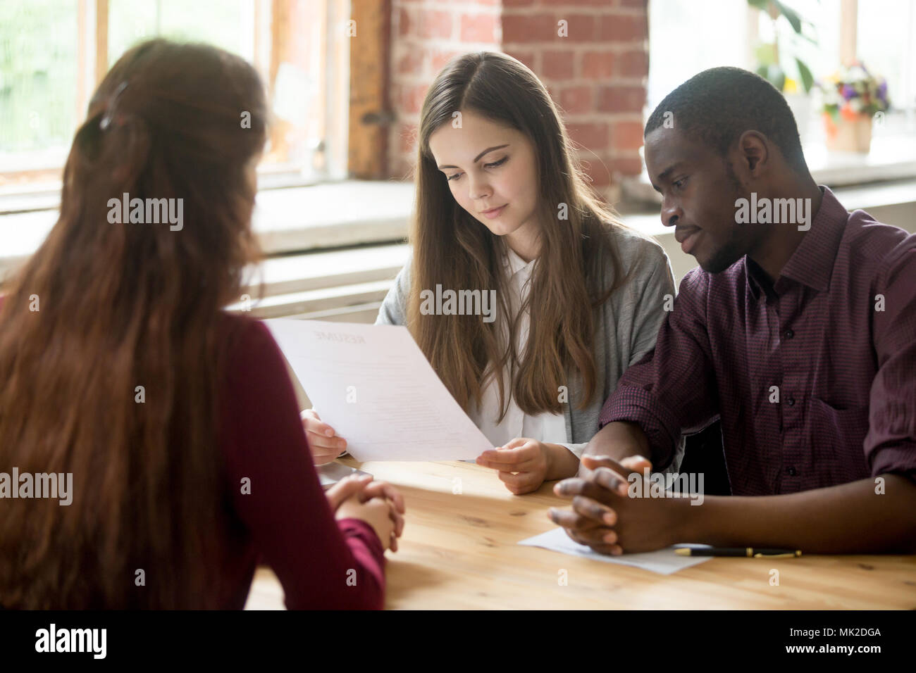 Multiracial managers reading applicant resume during hiring - Stock Image