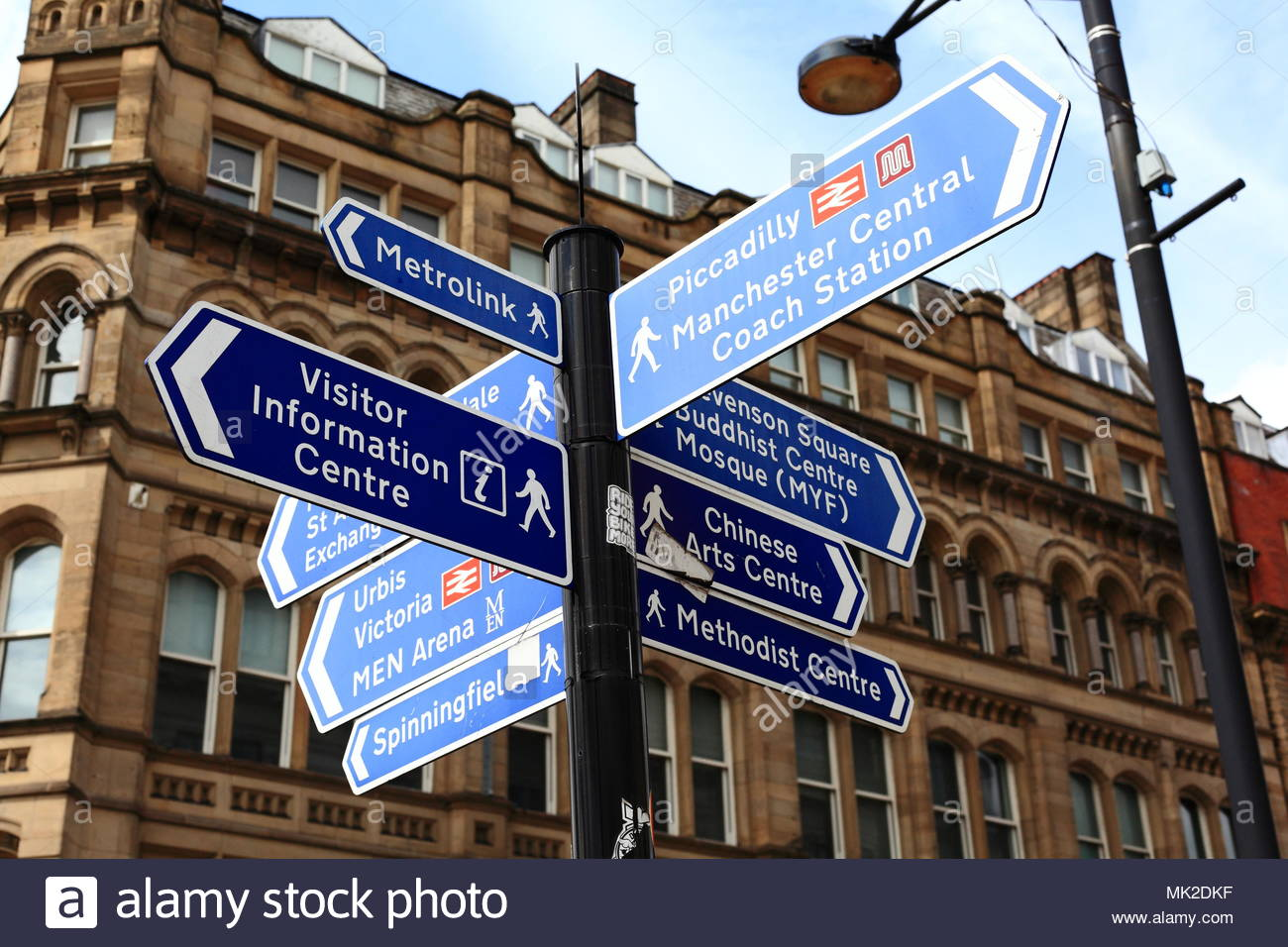 Multiple Information Signs Fixed To A Pole Displaying Which Direction To Take To Various Points Of Interest In Manchester Centre Manchester May 2018 - Stock Image