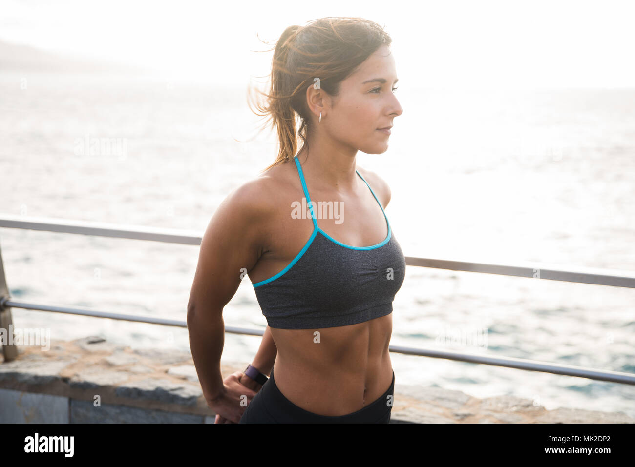 Strong young woman looking out at the sea in a grey tank top with blue edges and her hair tied back - Stock Image