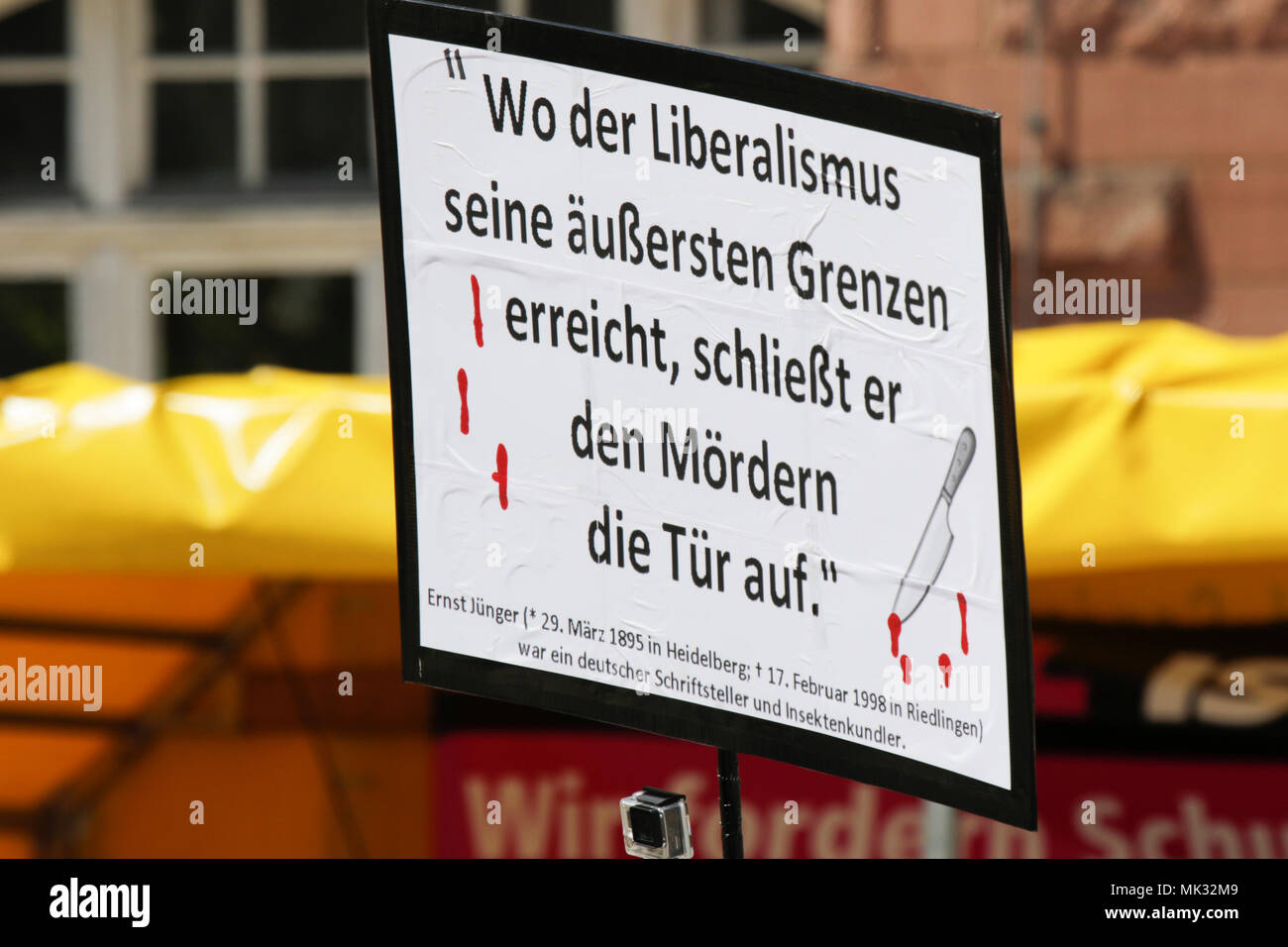 Germersheim, Germany. 6th May 2018. A right-wing protester holds up a sign that reads 'When liberalism reaches its final limits, it will open the door to murderers'. Around 100 from different right-wing organisations protested in the city of Germersheim against Angela Merkel and for the security of women and children, which they see at risk by refugees and foreigners. They also called for the introduction of mandatory age checks (DNA test) by underage refugees. Credit: Michael Debets/Alamy Live News - Stock Image