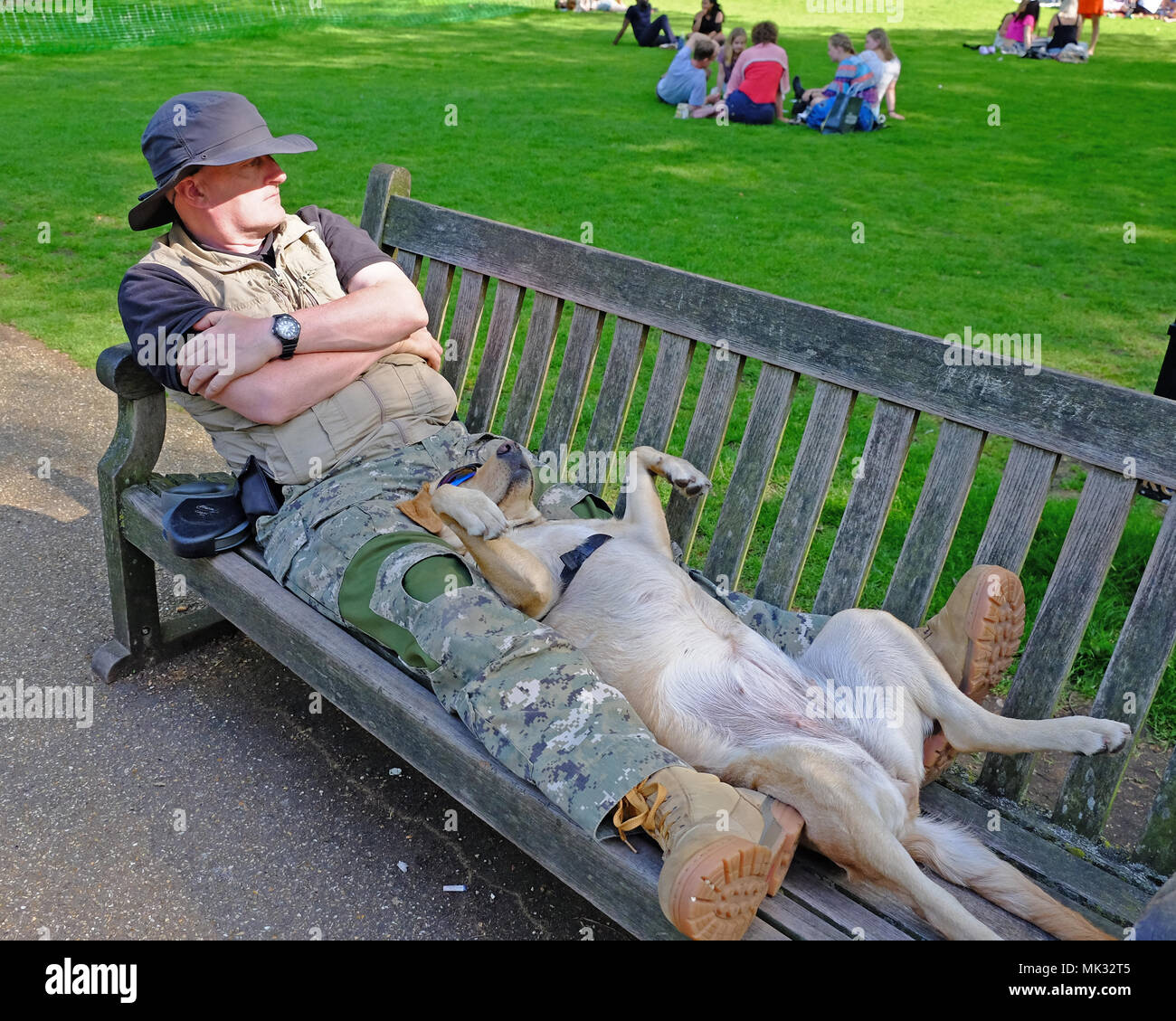 London Weather. St. James Park, London, UK, 6th May, 2018.  Dog with sunglasses on enjoys a nap in the park along with his human during the Heat Wave on this Bank Holiday Weekend. Credit: Judi Saunders/Alamy Live News - Stock Image