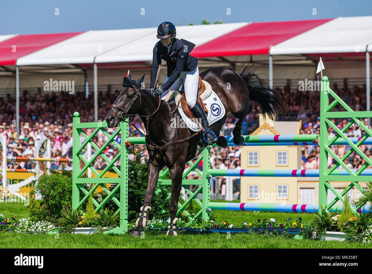 Gloucestershire, UK. 6th May, 2018. Jonelle Price (NZL) clears the last fence in the show jumping phase of the Mitsubishi Motors Badminton Horse Trials on her mount Classic Moet following her storming round of Cross Country yesterday. The smile says it all Jonelle who is married to fellow New Zealand three day eventer Tim Price had her first baby in August 2017. The couple are based near Marlborough in Wiltshire Credit: David Betteridge/Alamy Live News - Stock Image