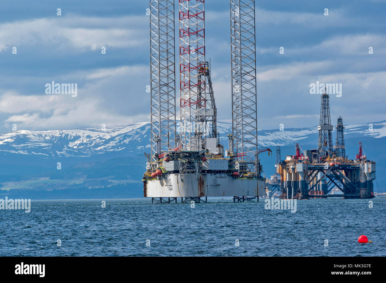 CROMARTY FIRTH SCOTLAND TALL OIL RIG OR DRILLING PLATFORM BAUG AND DECOMMISSIONED OIL RIG WITH SNOW COVERED HILLS Stock Photo