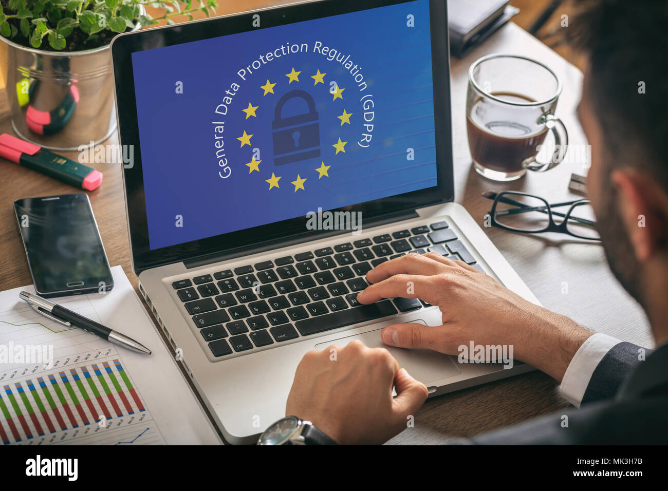 EU GDPR. Man working with a computer, General Data Protection Regulation and European Union flag on the screen - Stock Image