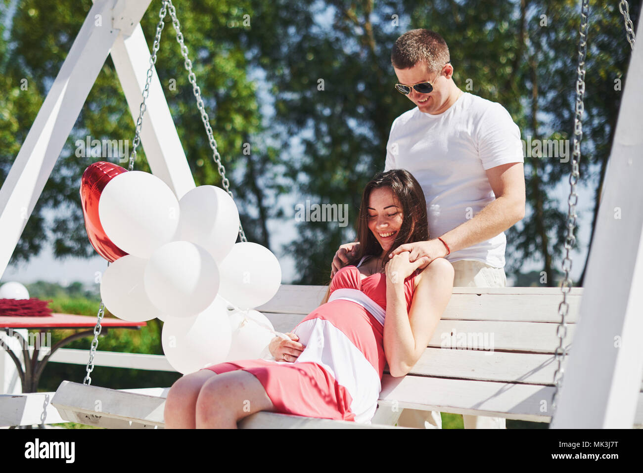 26c2a6fbe waiting baby. pregnant woman with beloved husband sit on a bench ...