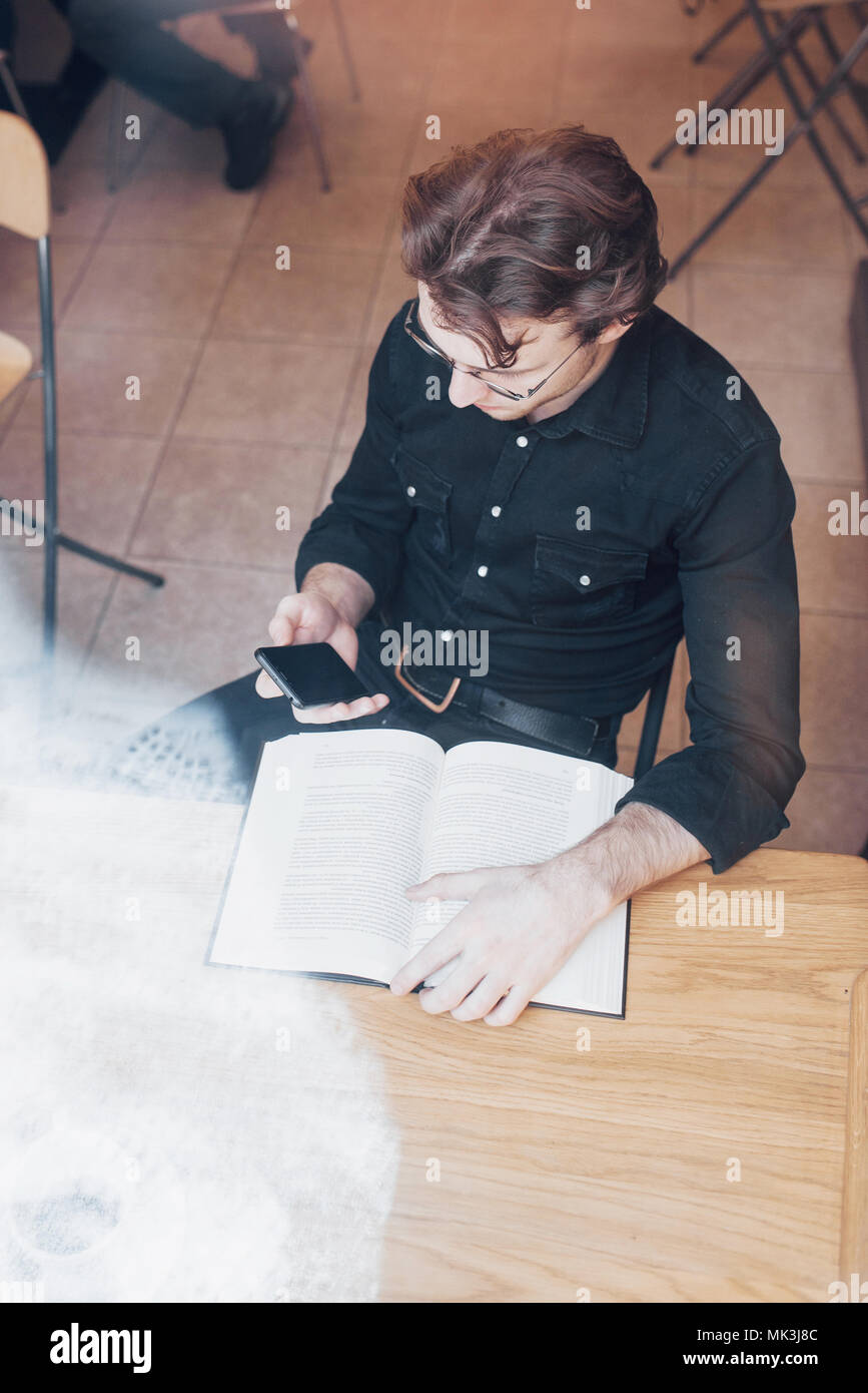 Young entrepreneur working in a cafe - Stock Image