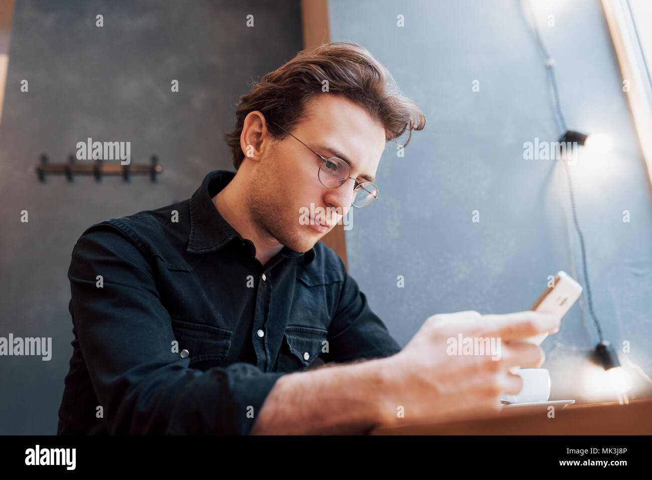 Close-up of man received good news on smart phone, Man resting in cafe and texting new mail messages, blurred background, shallow DOF - Stock Image