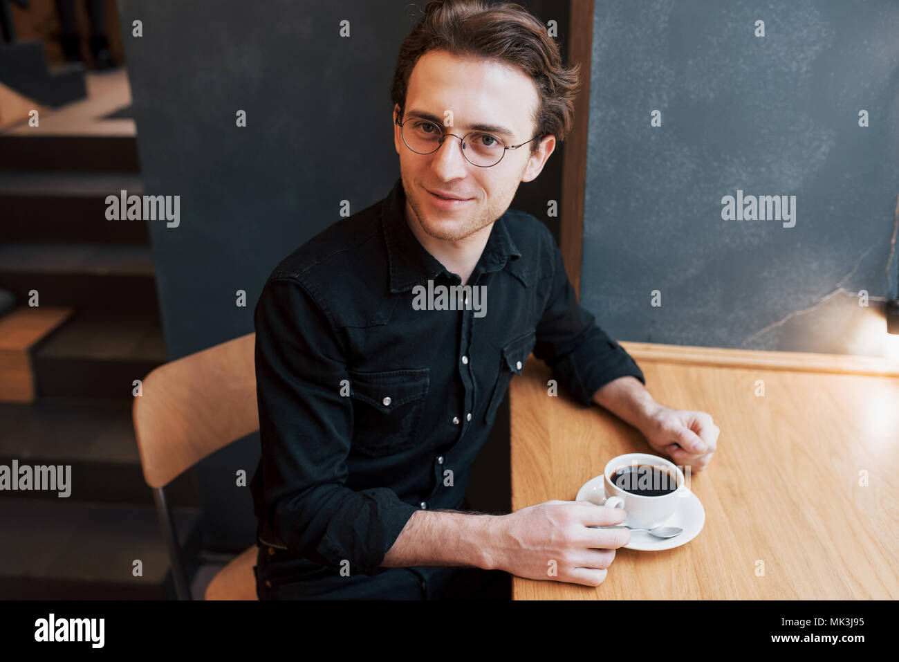 Handsome bearded man in checked shirt holding fork eating in cafe and smiling looking at camera - Stock Image