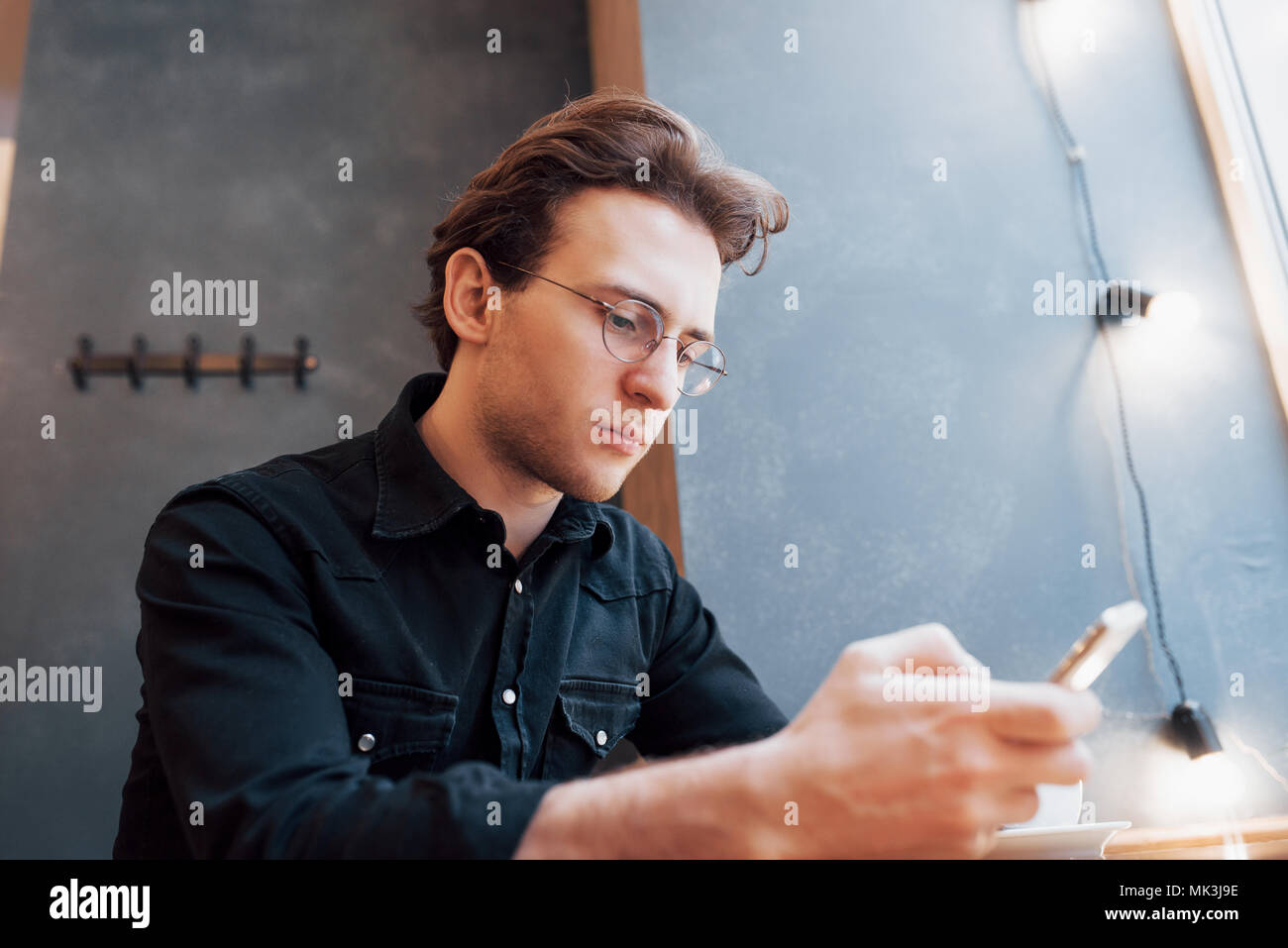 Portrait handsome bearded man headphones watching video mobile phone modern loft studio.Man sitting in vintage chair,holding smartphone and relaxing.Horizontal, film effect, bokeh Stock Photo