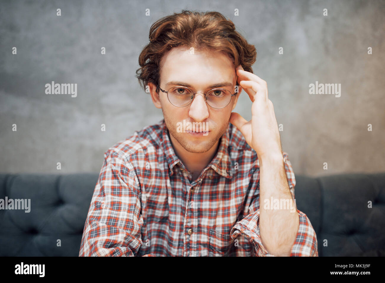 portrait of handsome and relaxed man sitting at a cafe and thinking, working remote, looking on the camera - Stock Image