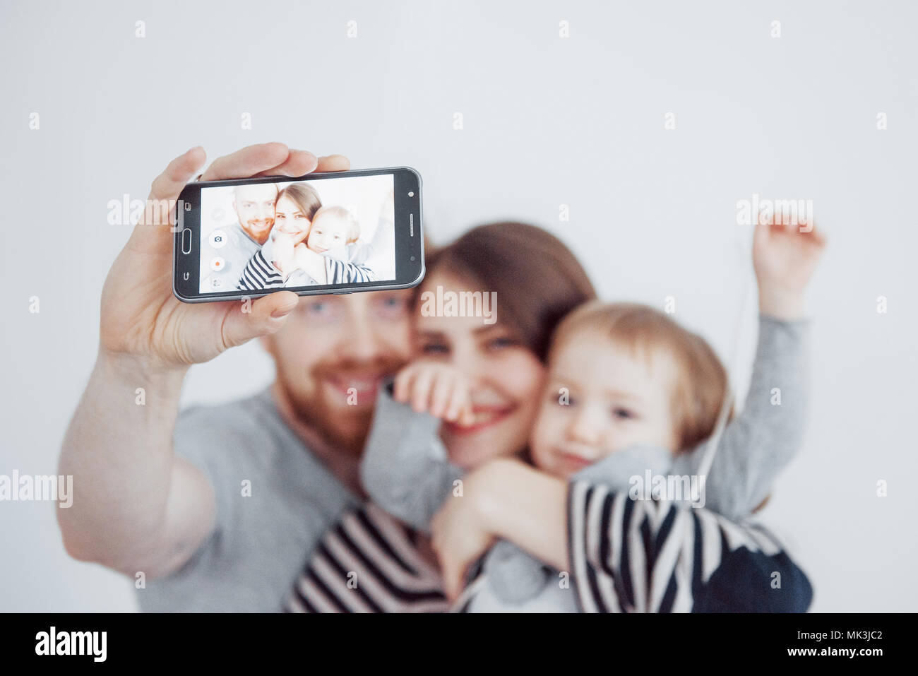 family, holidays, technology and people - smiling mother, father and little girl making selfie with camera over white background - Stock Image