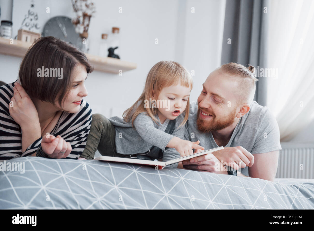 Father, Mother and Little Daughter Reading Children's Book on a Sofa in the Living Room. Happy big family read an interesting book on a festive day. Parents love their children - Stock Image