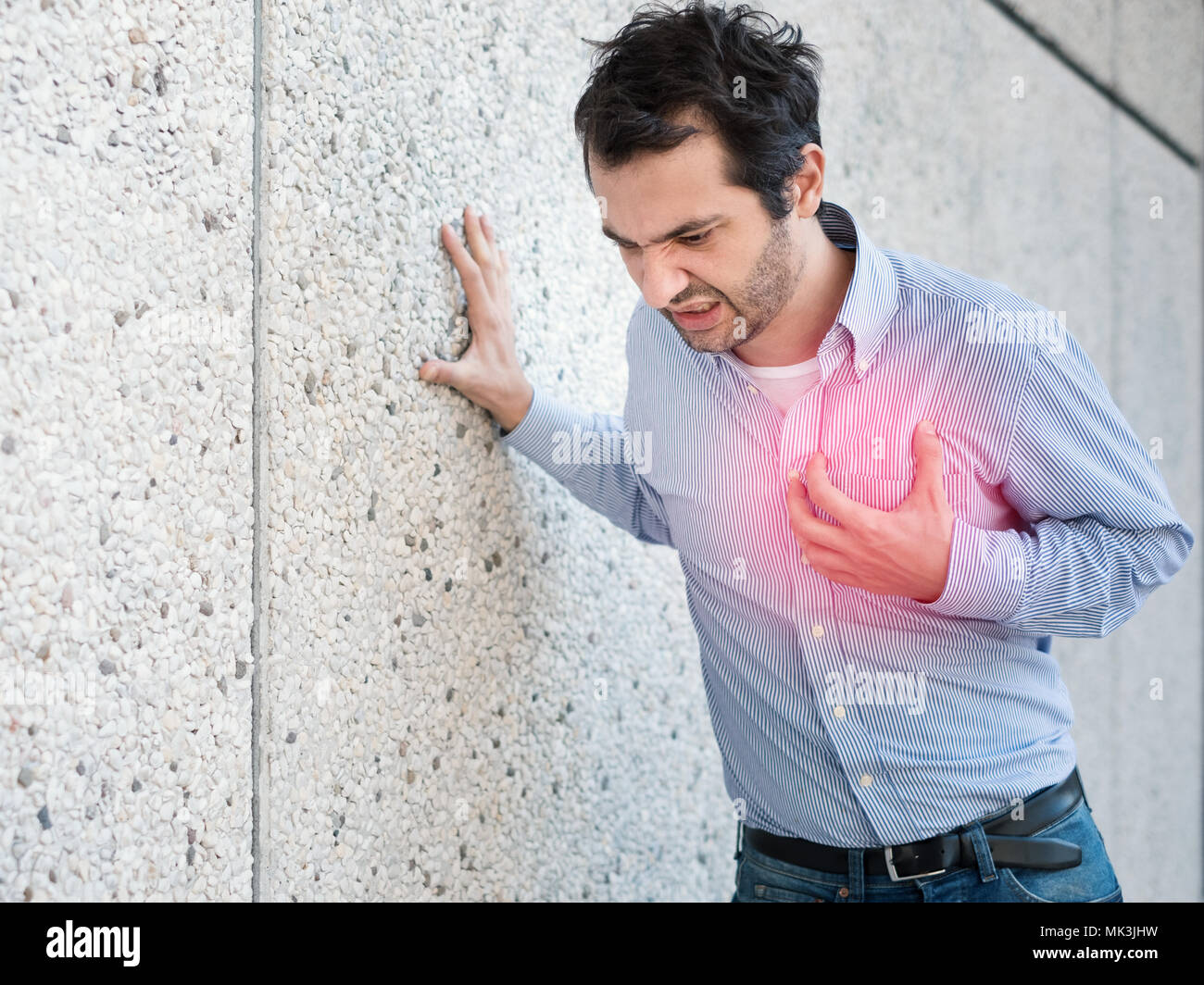 Man having a sudden heart attack and feeling bad - Stock Image