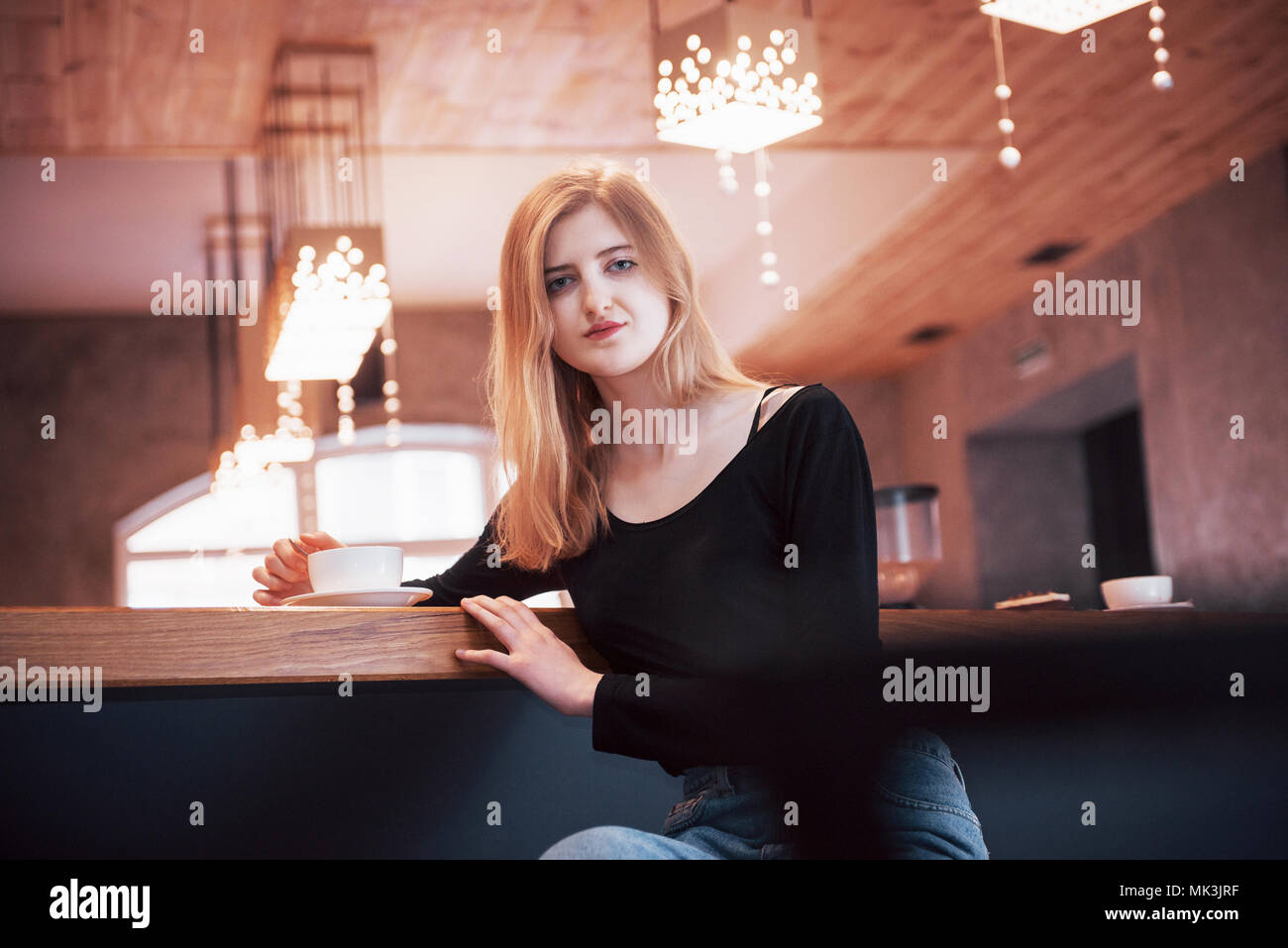 Happy smiling young woman using phone in a cafe. Beautiful girl in trendy spring colors - Stock Image
