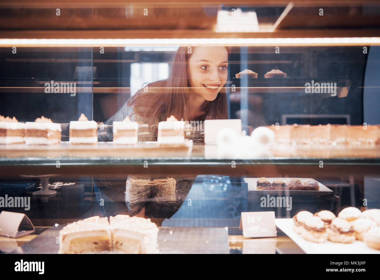 Smiling woman at camera through the showcase with sweet and cakes in modern cafe interior - Stock Image