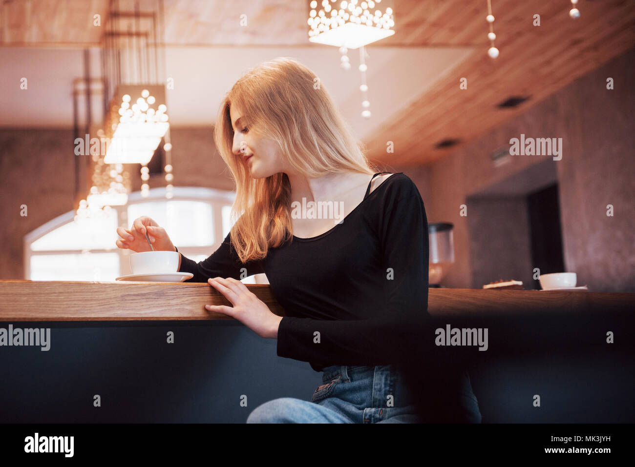 Smiling woman in cafe using mobile phone and texting in social networks, sitting alone - Stock Image