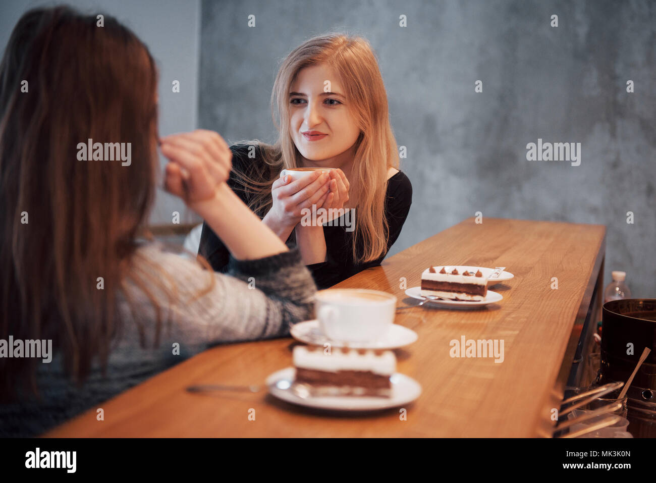 Toned picture of best friends having date in cafe or restaurant. Beautiful girls talking or communicating while drinking coffee - Stock Image