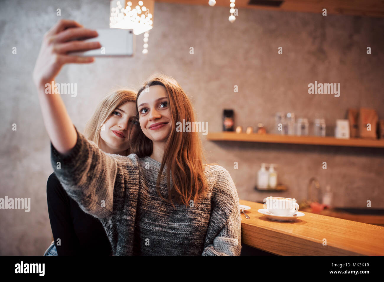Two friends drinking coffee in a cafe, taking selfies with a smart phone and having fun making funny faces. Focus on the girl on the left Stock Photo