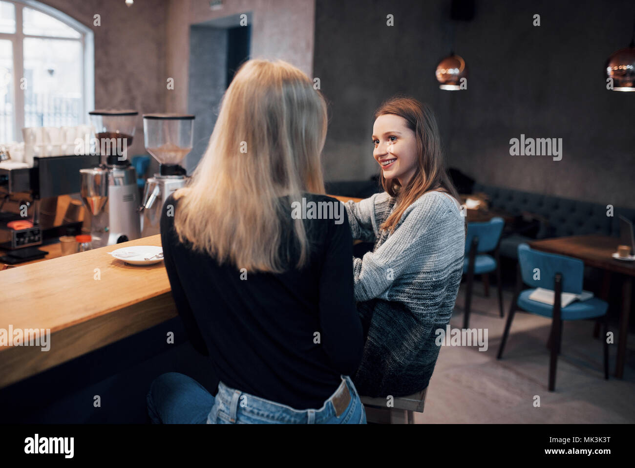 Two friends enjoying coffee together in a coffee shop as they sit at a table chatting - Stock Image