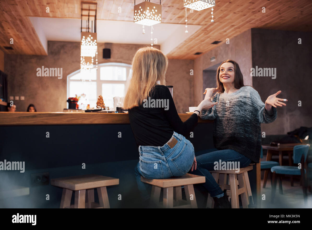 Two girl friends drinking coffee in the cafe - Stock Image