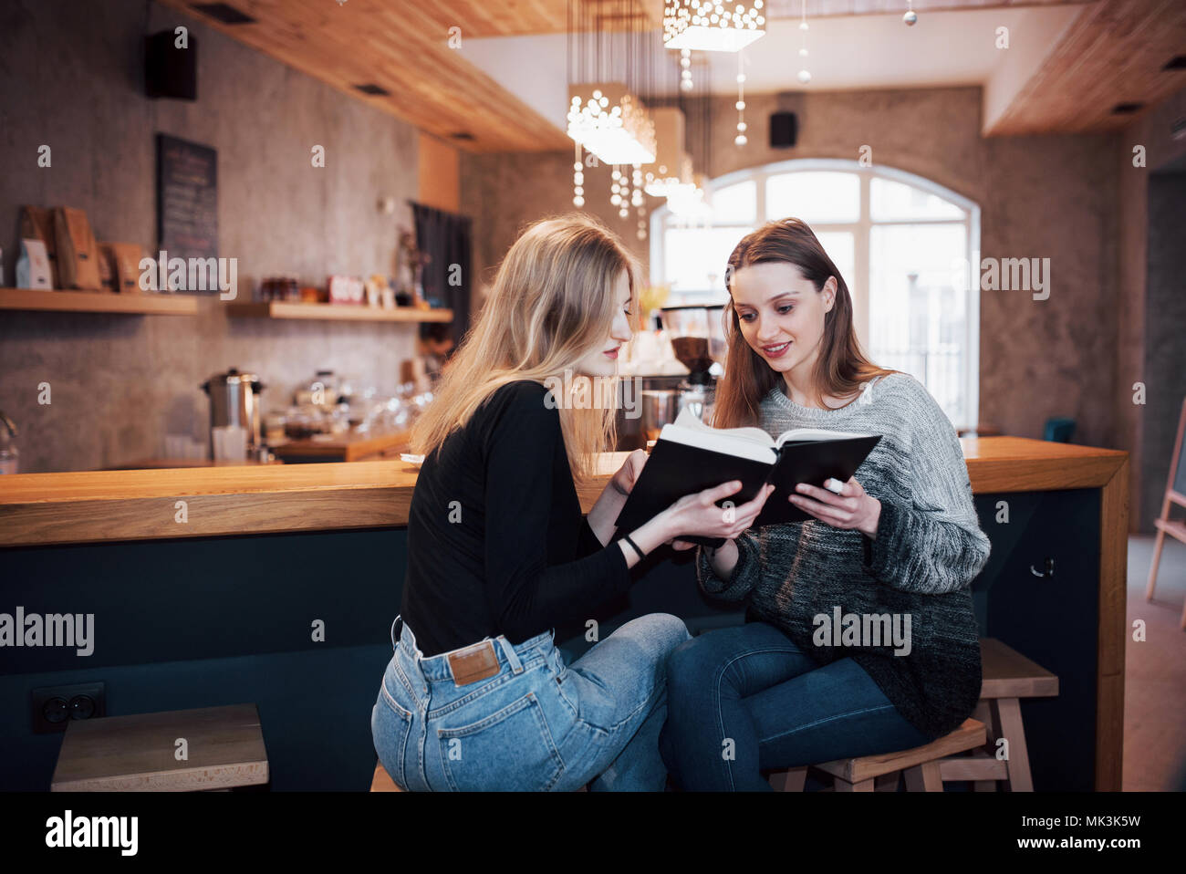 Two Girl`s absorbed in reading book during the break in cafe. Cute lovely young women are reading book and drinking coffee - Stock Image