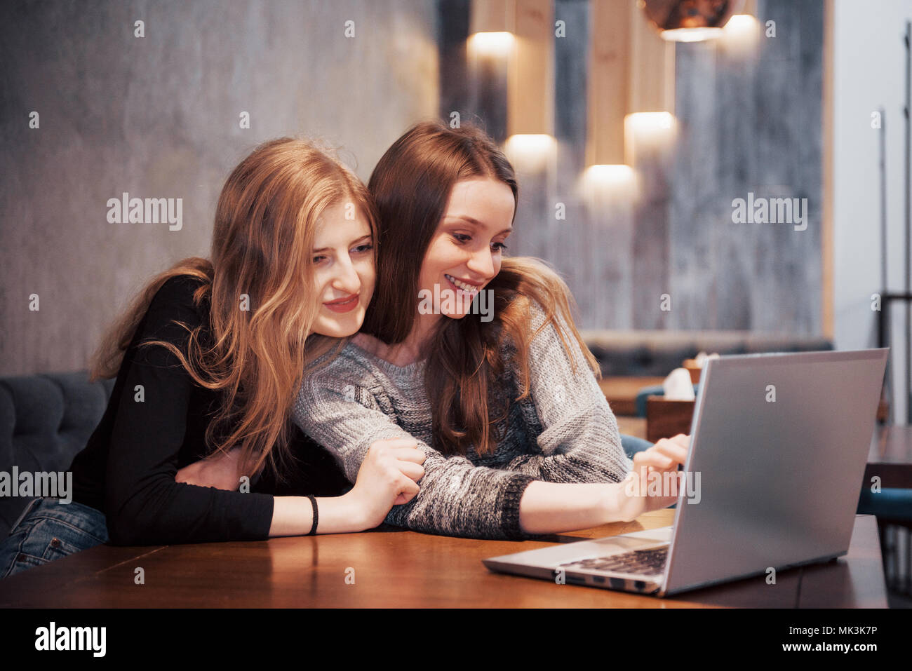 Two girls surfing the net, posting on social networks on a laptop computer and having fun - Stock Image
