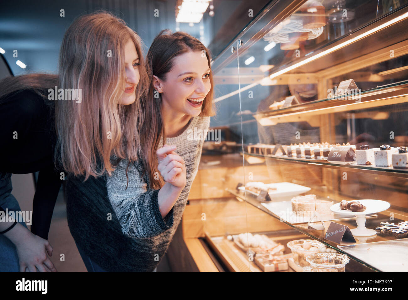 Two happy attractive girls choosing delicious ganaches, praline and chocolates - Stock Image