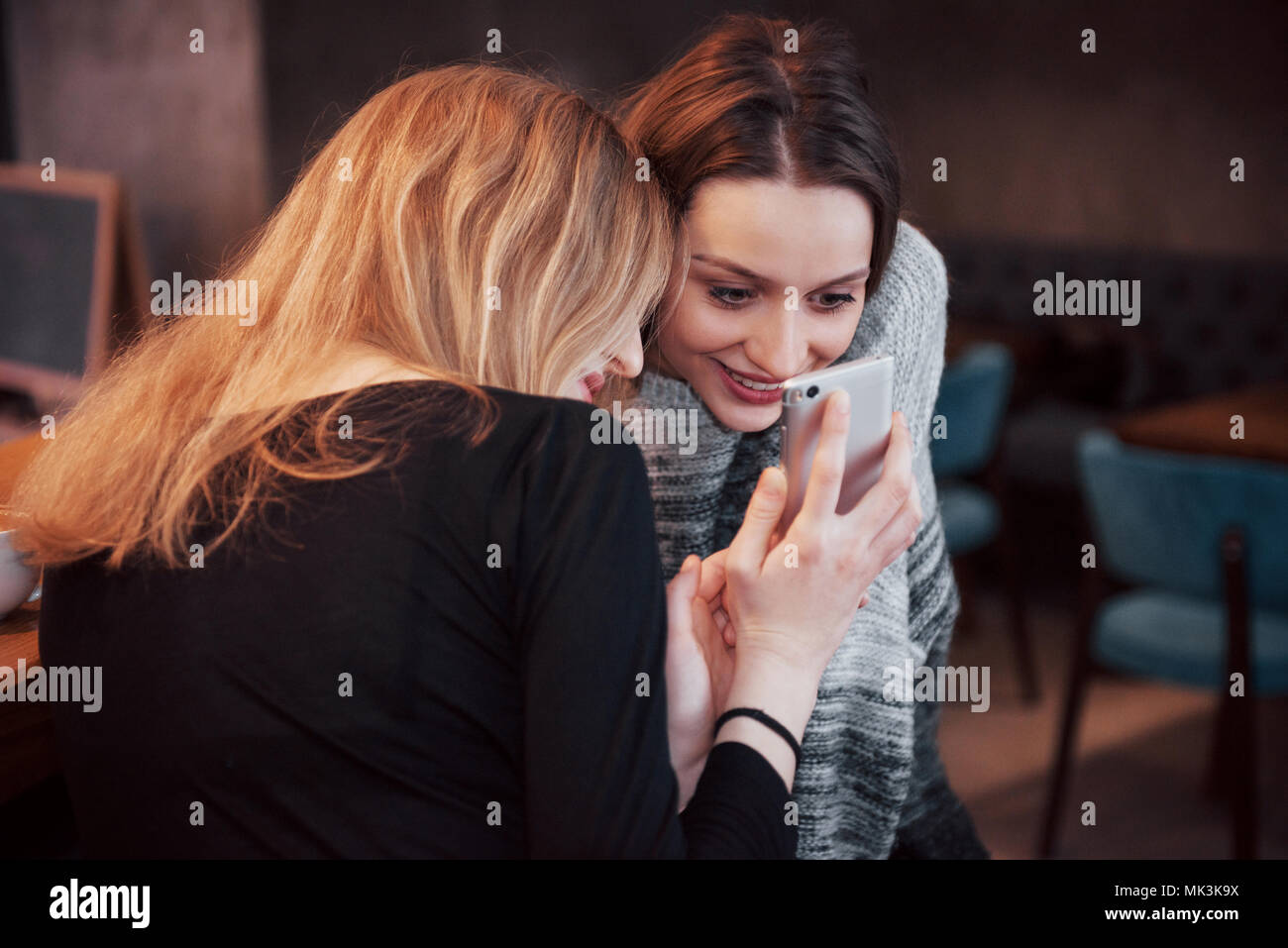 Two smiling friends reading funny online chat on modern telephone sitting with tasty coffee in restaurant.Hipster girls enjoying recreation time in cafe with hot beverages and messaging on cellular - Stock Image