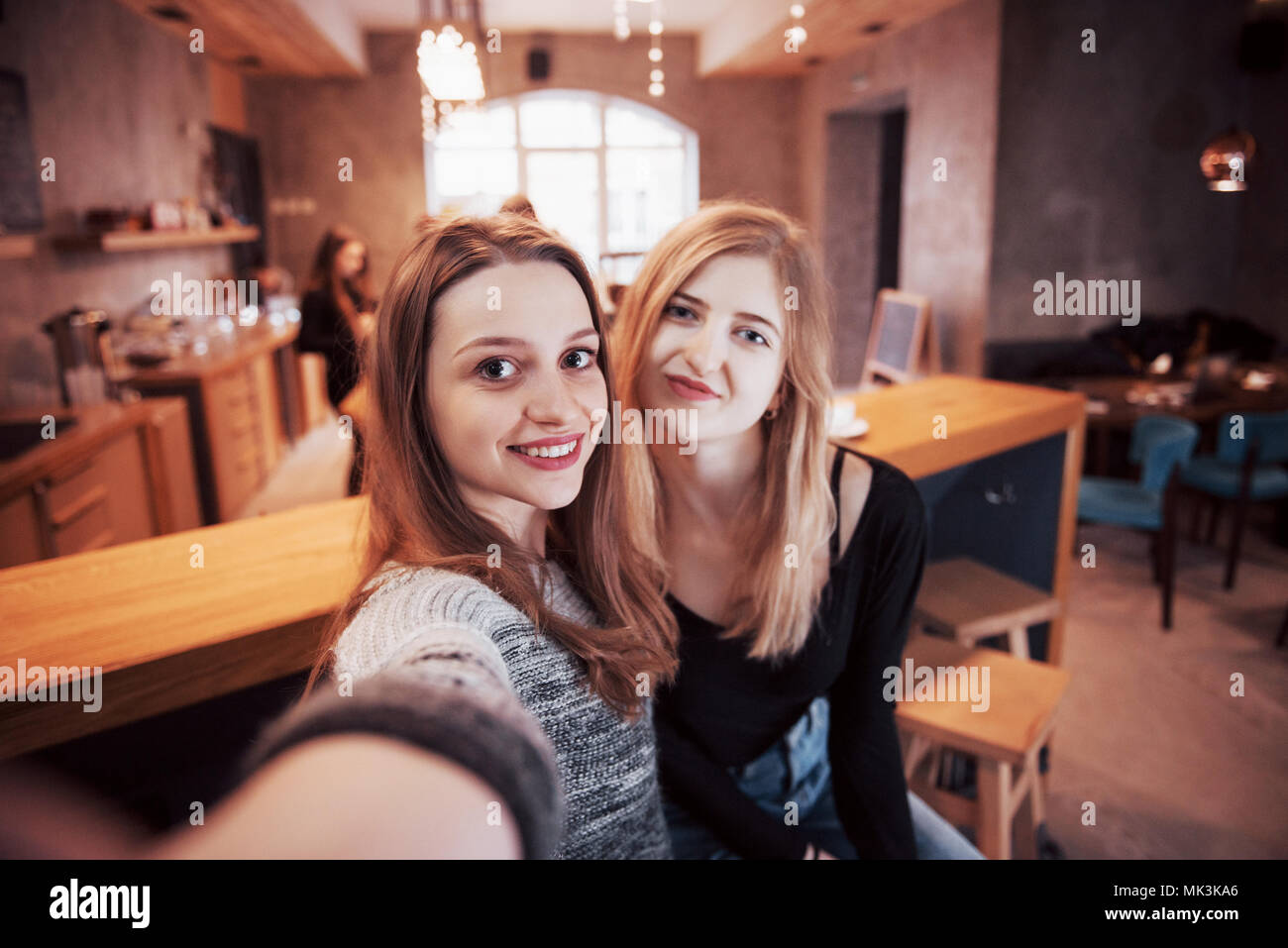 Two women friends sitting in cafe and make selfie - Stock Image
