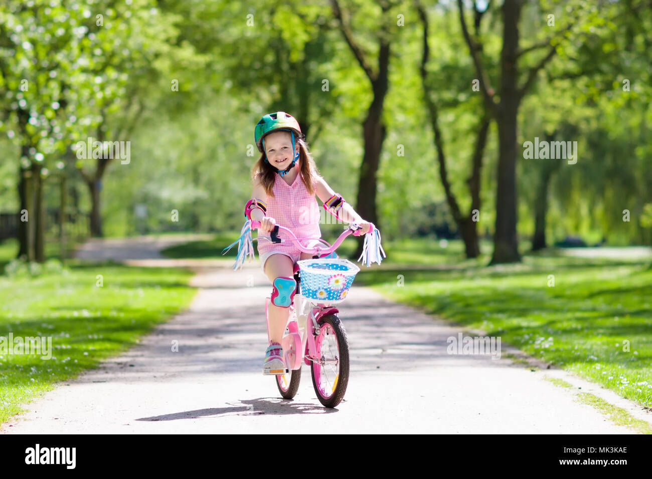c1753393d566 Child riding a bike in summer park. Little girl learning to ride a bicycle  without training wheels. Kindergarten kid on two wheeler bike. Active outdo
