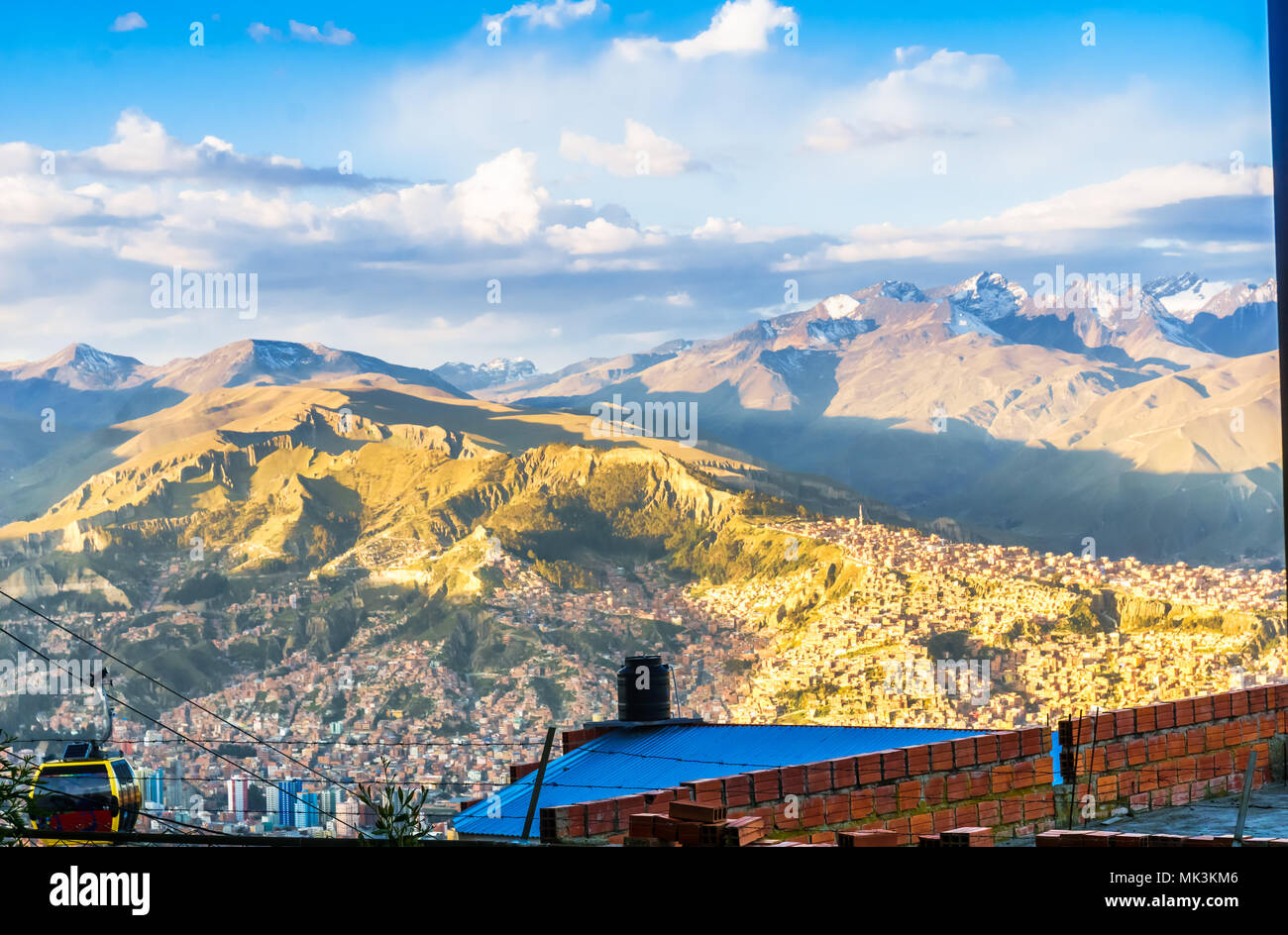 View on cityscape of la Paz and yellow cable car in front of illimani mountain - Bolivia - Stock Image