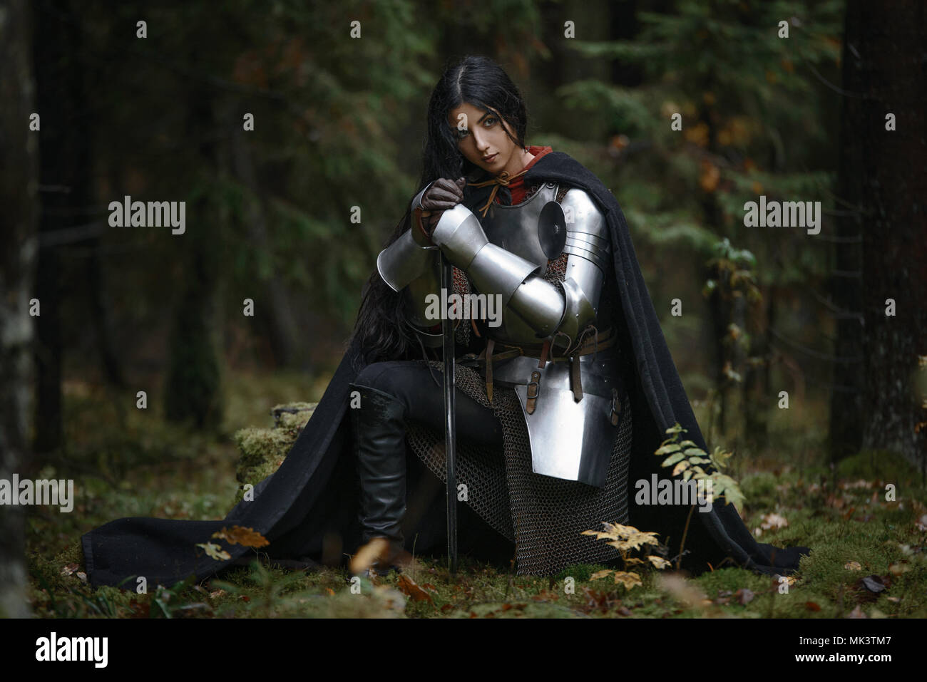 A beautiful warrior girl with a sword wearing chainmail and armor in a mysterious forest Stock Photo