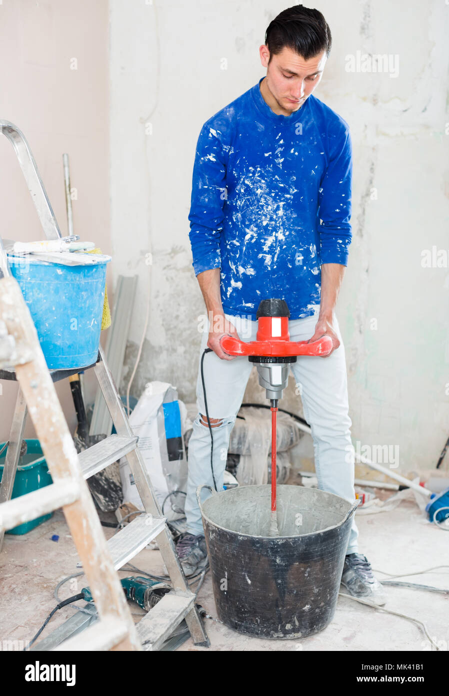 builder mixing plaster in bucket using electric mixer in repairable room Stock Photo