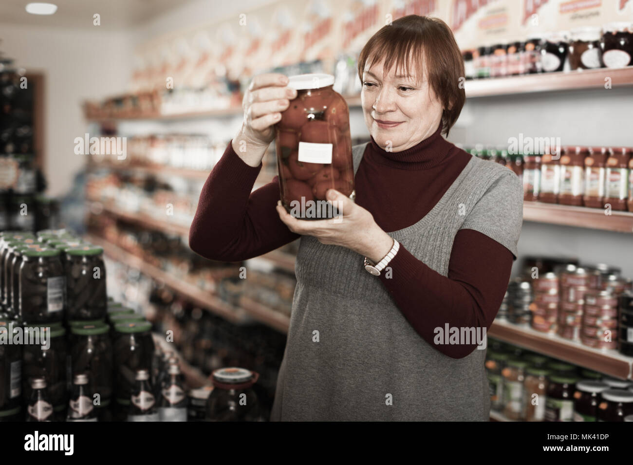 Mature woman in the store choosing preserved food of tomatoes - Stock Image