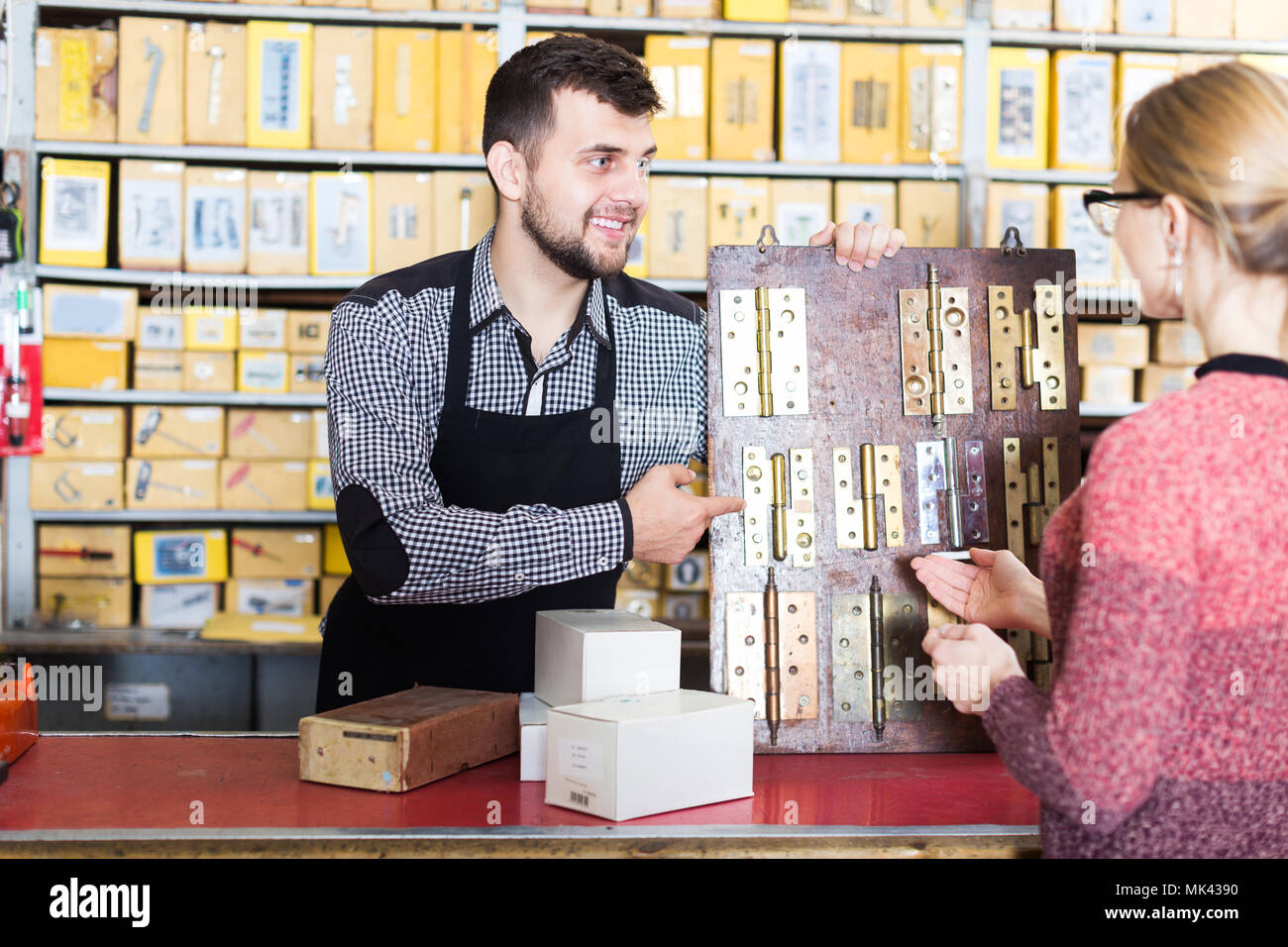 Male seller offering door hinges to female customer in houseware shop  sc 1 st  Alamy & Male seller offering door hinges to female customer in houseware ...