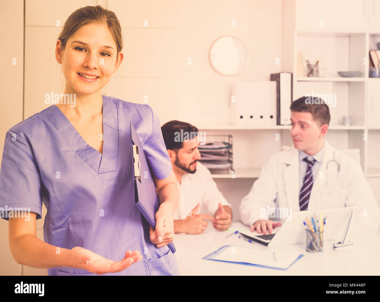 Female doctor making welcome gesture, politely inviting patient in medical office - Stock Image