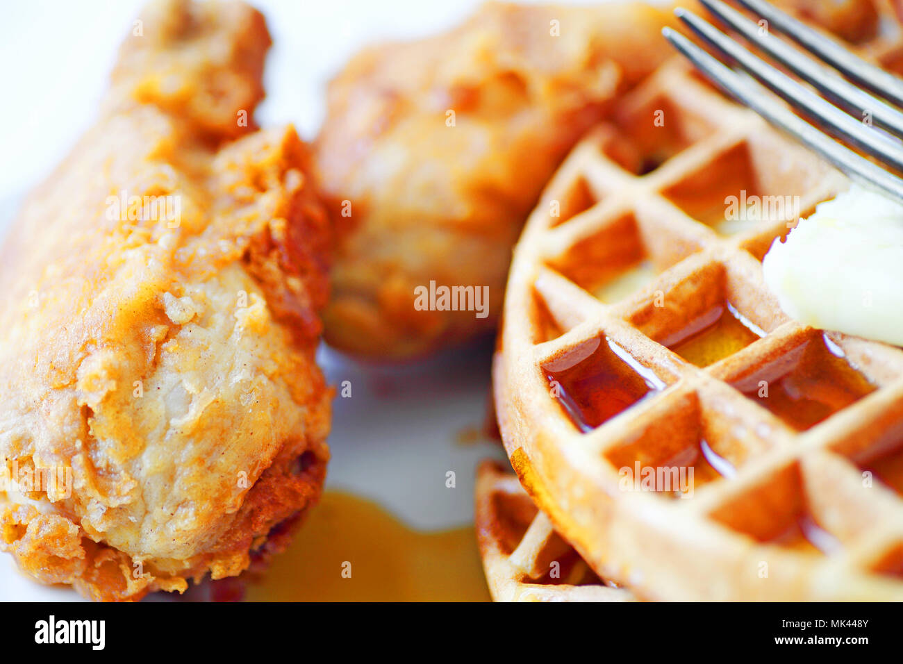 Closeup of fried chicken legs, Belgian waffles, butter and maple syrup with a fork - Stock Image