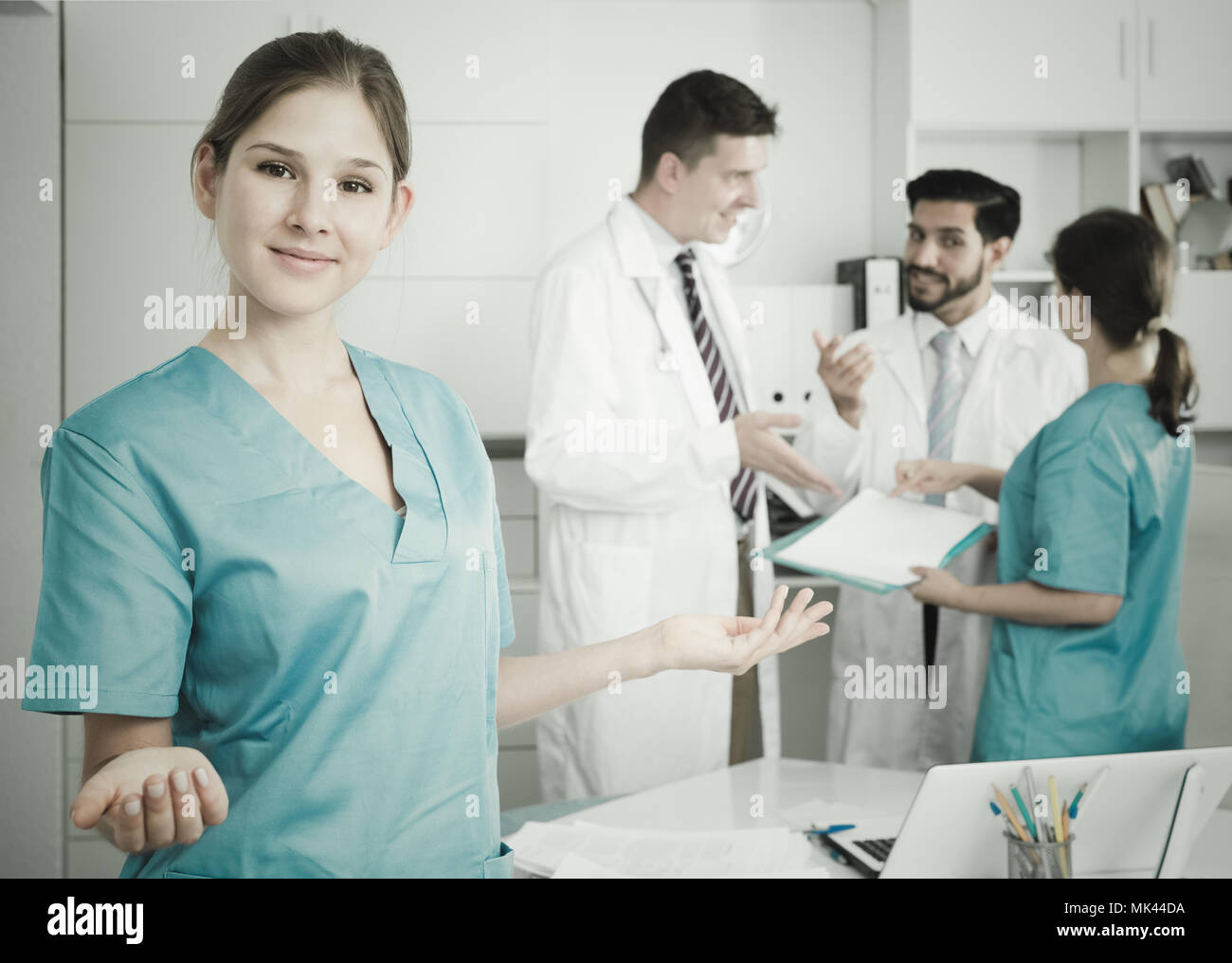 Young smiling female doctor welcoming patient to clinic - Stock Image