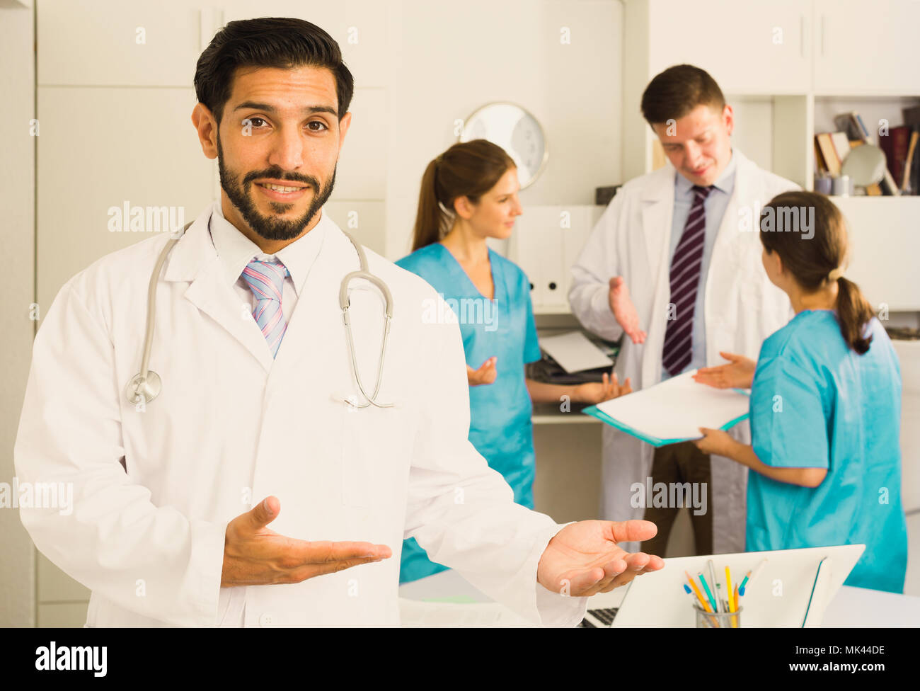 Experienced smiling male doctor welcoming patient to clinic - Stock Image