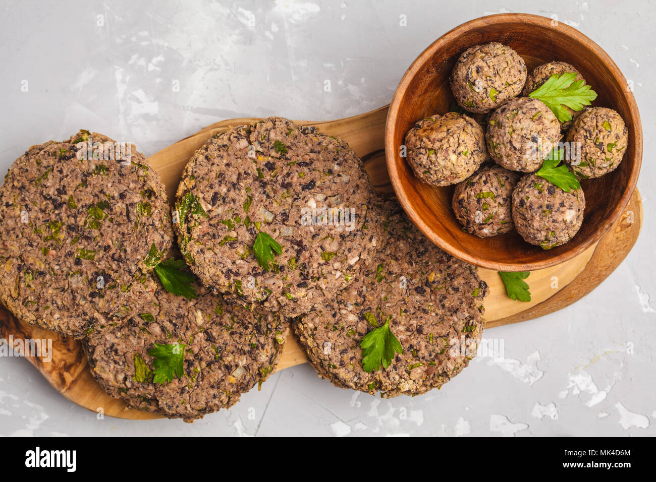 Vegan beans burgers (cutlets) and meatballs with parsley on a wooden board, copy space. Healthy vegan food concept. - Stock Image