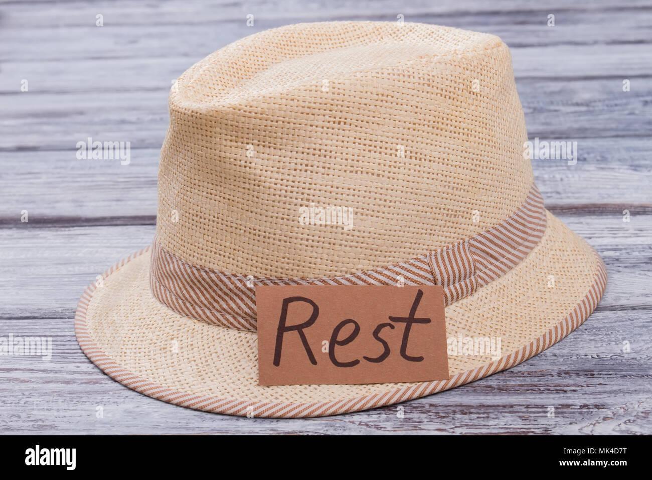 Beige straw hat for rest on the beach. Dark wooden desk surface background. 1f6378d2dd35