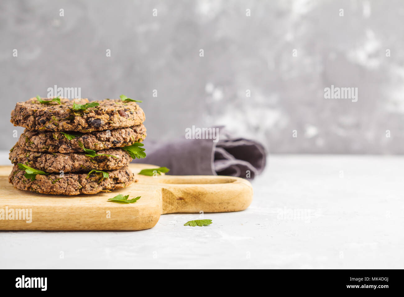 Vegan beans burgers (cutlets) with parsley on a wooden board.  Healthy vegan food concept. - Stock Image