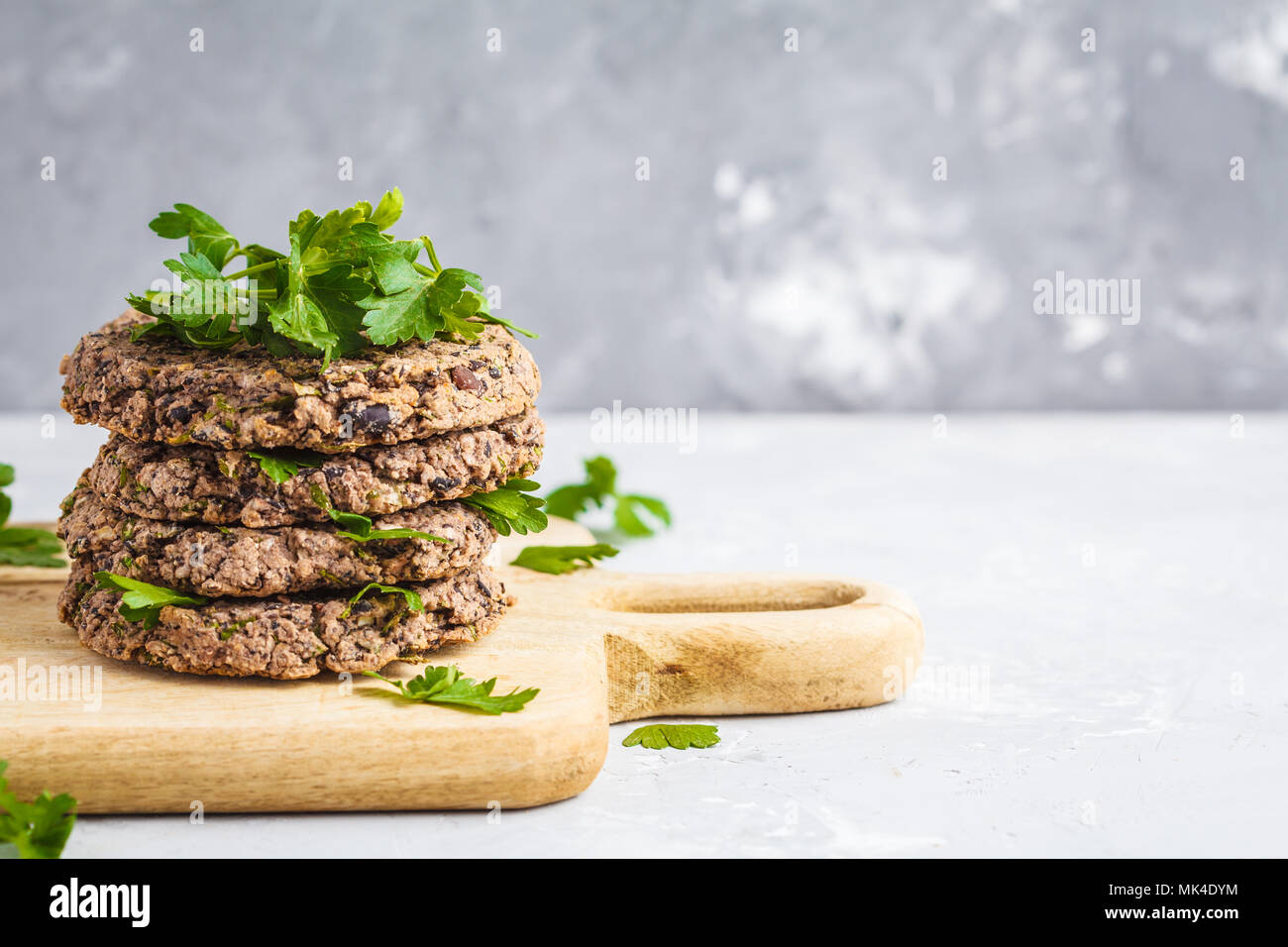 Vegan beans burgers (cutlets) with parsley on a wooden board.  Healthy vegan food concept. Stock Photo