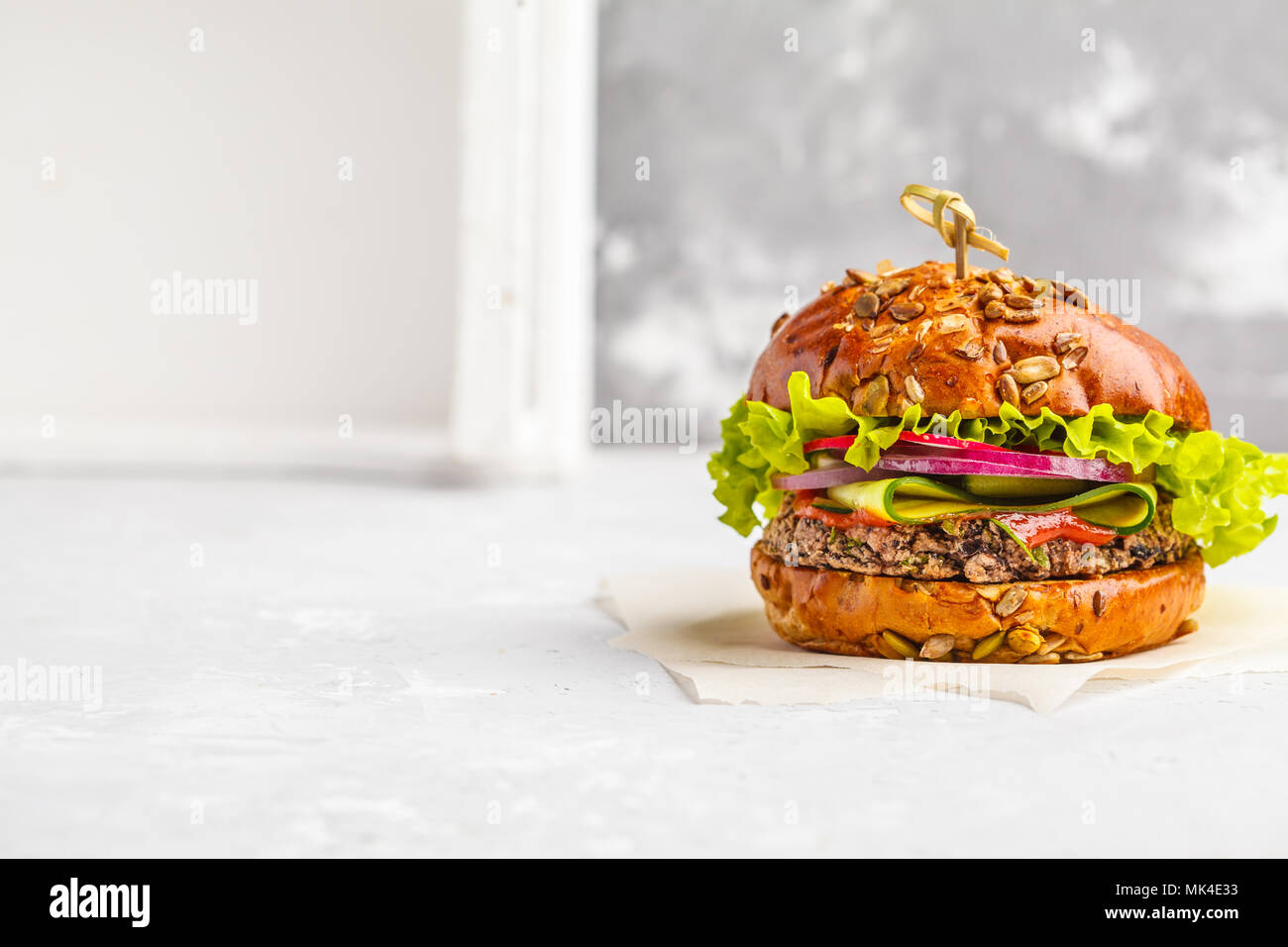 Vegan bean burger with vegetables and tomato sauce, copy space. Healthy vegan food concept. - Stock Image