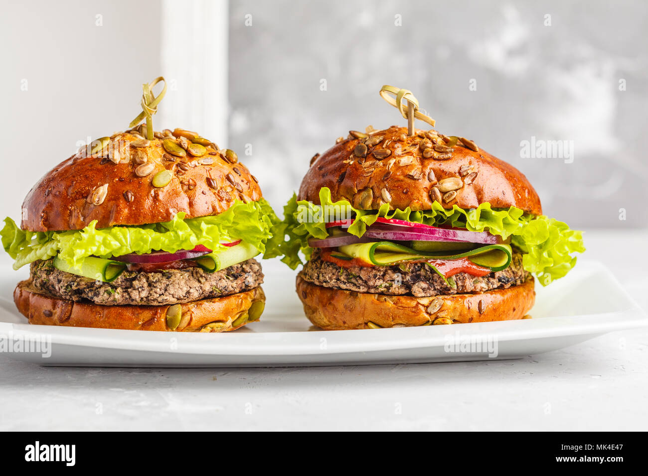 Vegan bean burgers with vegetables and tomato sauce on white dish, copy space. Healthy vegan food concept. Stock Photo