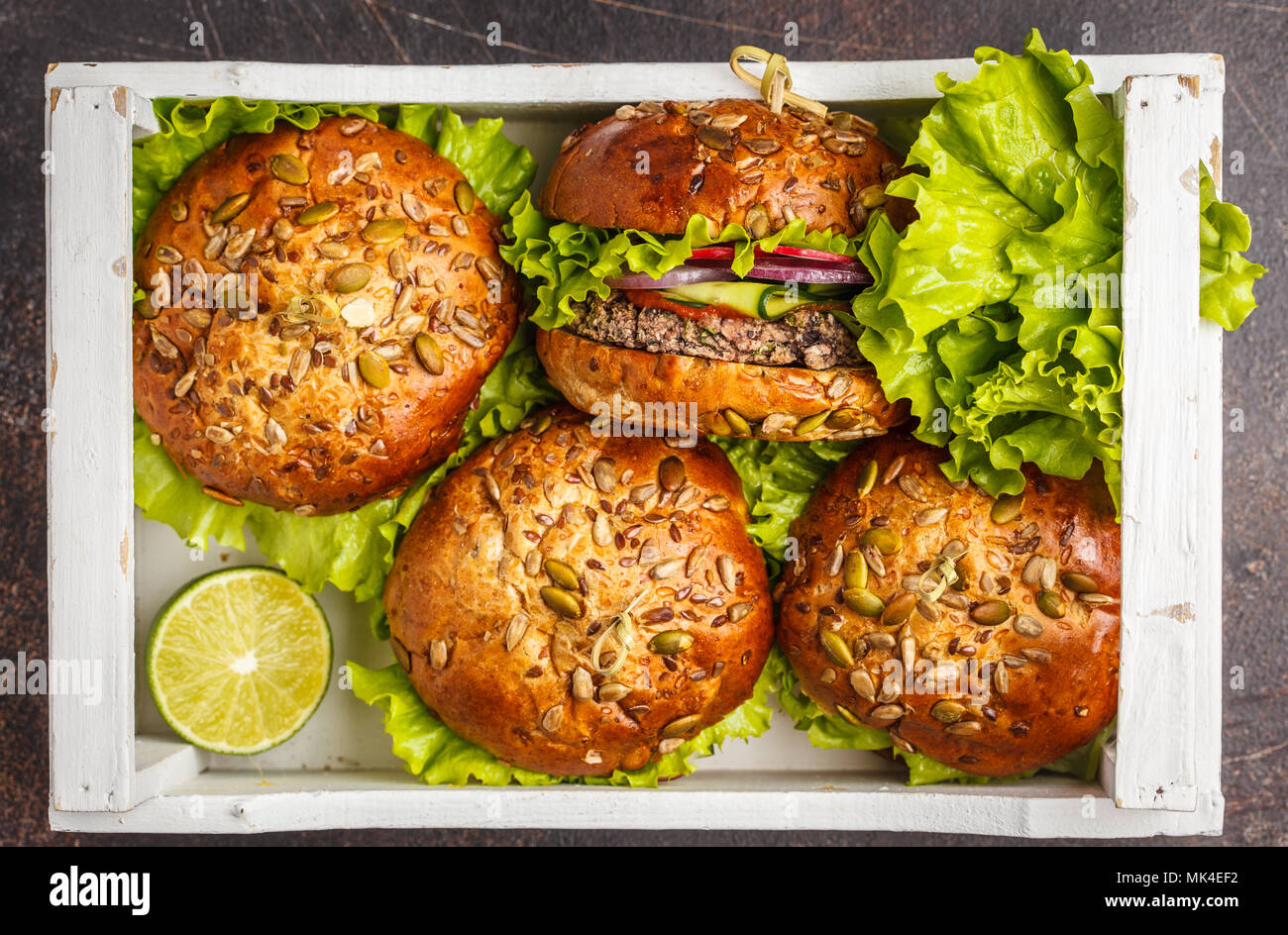 Vegan bean burger with vegetables and tomato sauce in white wooden box, top view. Healthy vegan food concept. - Stock Image