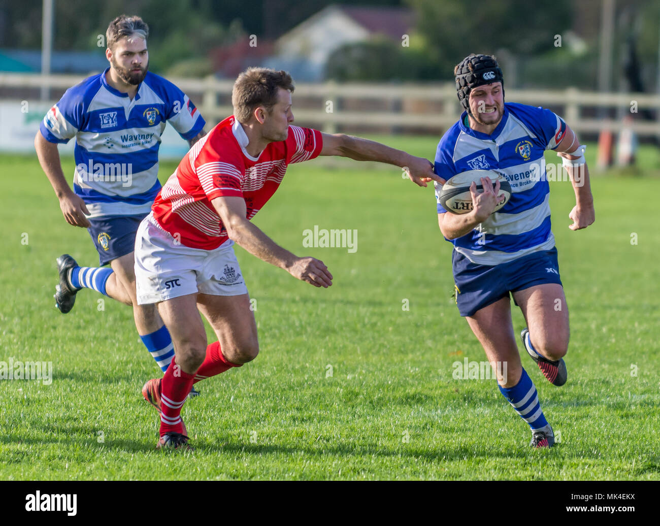 Amateur rugby match - attacker with ball in one hand sprints passed tackler who is reaching out, with an attacking teammate in the background - Stock Image
