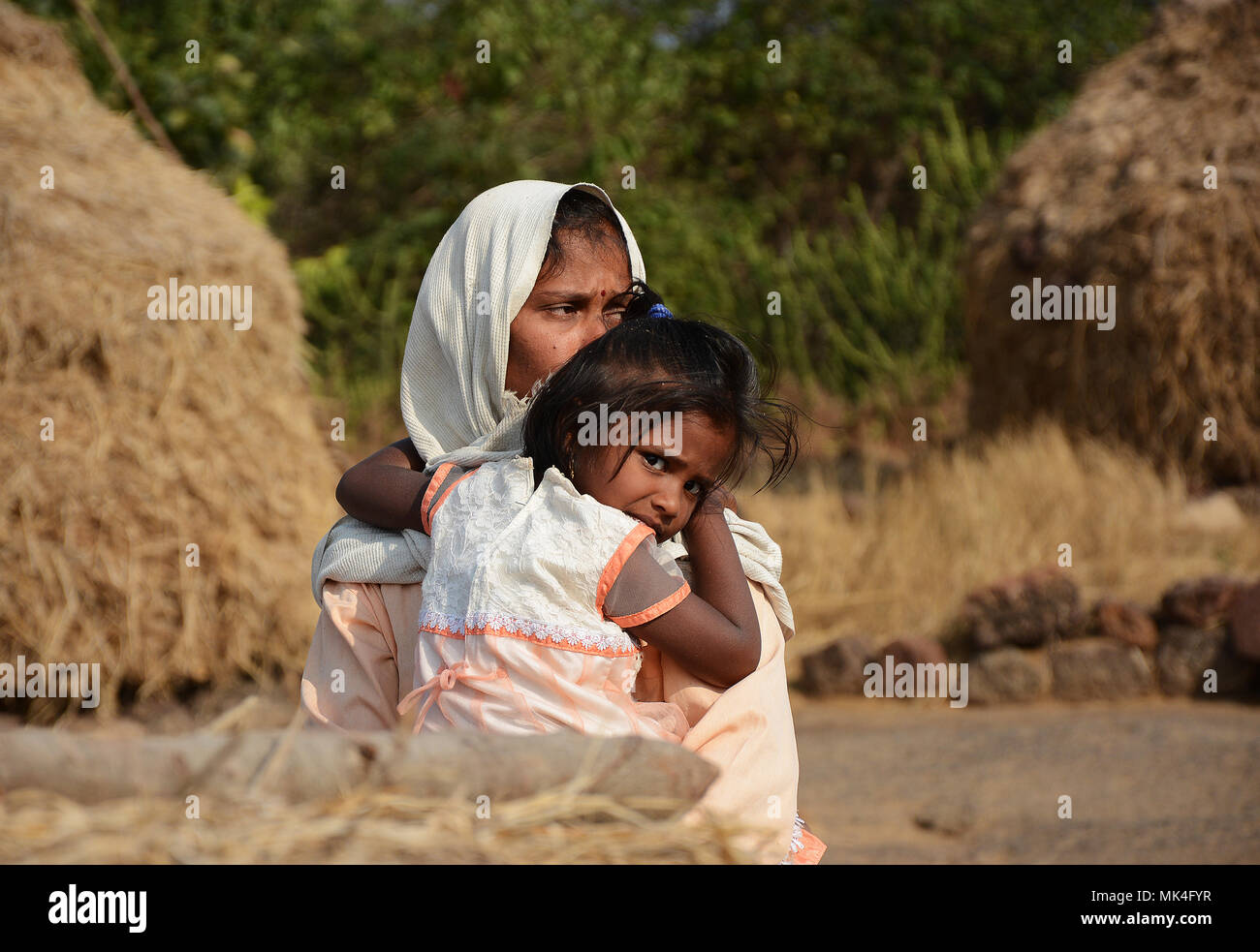 A mother lovingly holding her child giving her a cuddle, Rural area, India. - Stock Image