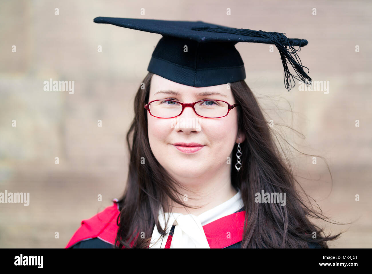 Mature Plus-Size Female Graduate Wearing Cap & Gown with Glasses ...