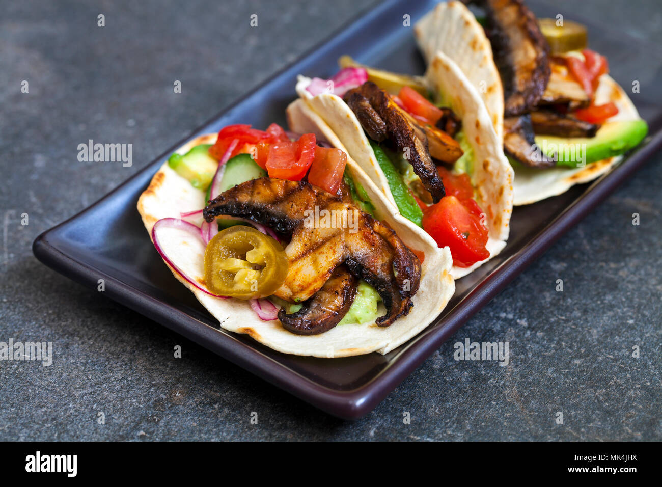 Vegan tortillas with mushrooms, avocado, pickled onions and cucumber - Stock Image